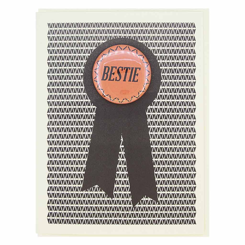 "This card looks like a prize ribbon. Features a 1½"" button with the text 'Bestie' that can be taken off and proudly worn by the recipient. Card measures 4¼"" x 5½"", comes with a cream envelope & is blank inside. Designed by The Regional Assembly of Text."