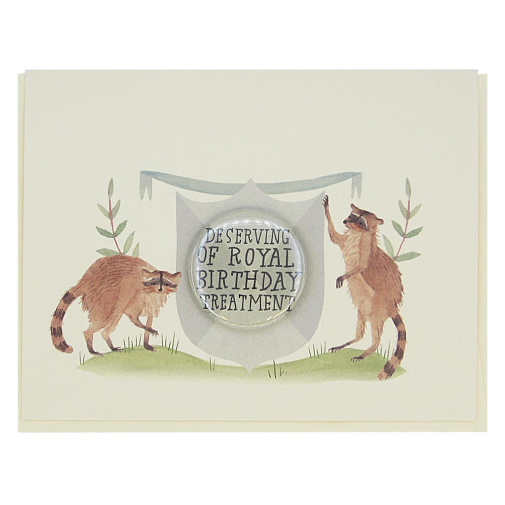 "This beautiful birthday card features a watercolour painting of two raccoons on either side of a crest. There is a 1½"" button in the middle of the crest which reads 'deserving of royal birthday treatment'. The button can be taken off and worn by the recipient. Card measures 4¼"" x 5½"", comes with a cream envelope & is blank inside. Designed by The Regional Assembly of Text."