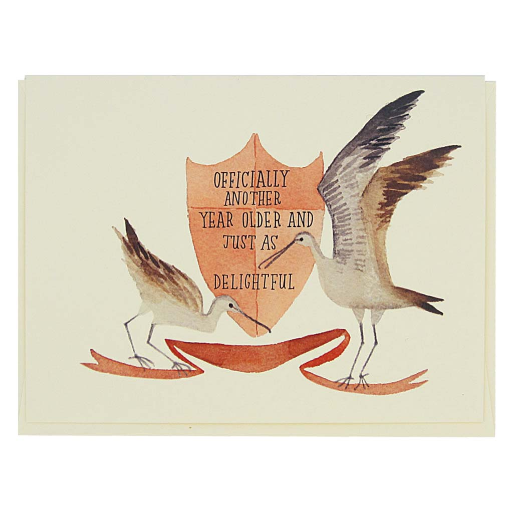 "This beautiful and birthday card features a watercolour painting of sandpipers surrounding a crest which reads 'officially another year older and just as delightful' Card measures 4¼"" x 5½"", comes with a cream envelope & is blank inside.Designed by The Regional Assembly of Text."