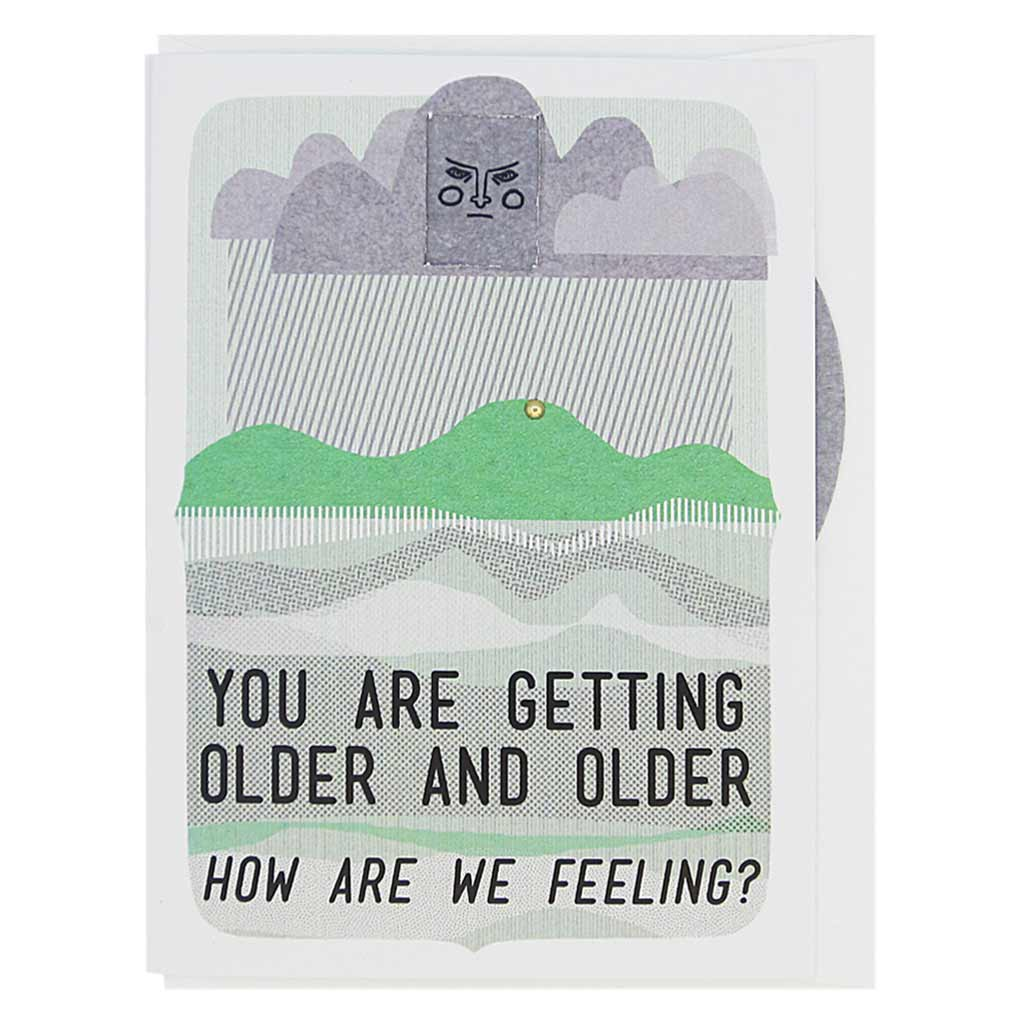 "This birthday card features a landscape with a cloud brewing above the mountains. The cloud has a face and you can turn a wheel to find an appropriate facial expression for this occasion. The card reads, 'You are getting older and older… how are we feeling?' There are 8 faces to choose from: sad, mad, worried, smiling, winking, frowning etc. Card measures 4¼"" x 5½"", comes with a white envelope & is blank inside. Designed by The Regional Assembly of Text."