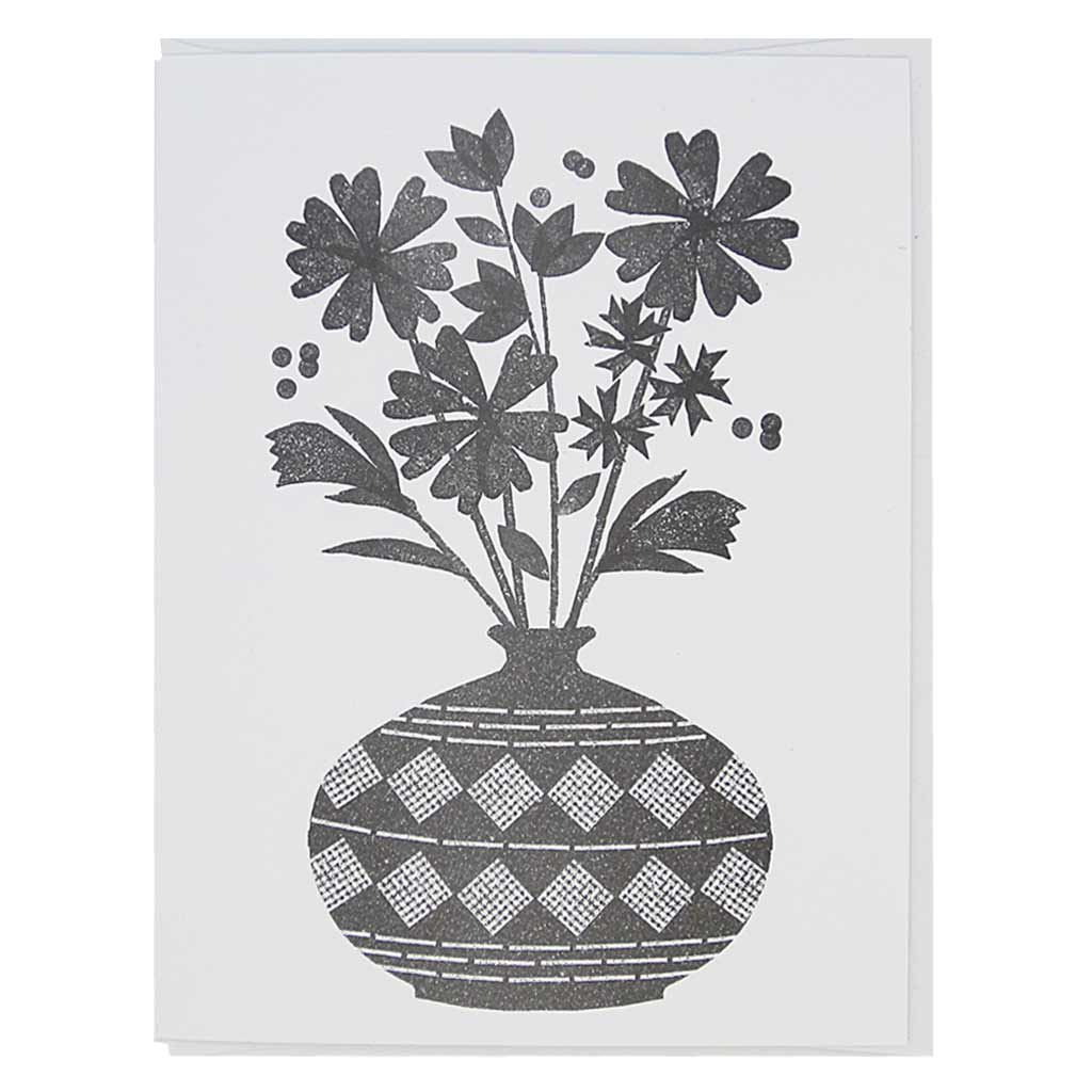 "This greeting card is a black and white image of a bouquet of flowers in a vase. It has a lino cut feel. Card measures 4¼"" x 5½"", comes with a white envelope & is blank inside. Designed by The Regional Assembly of Text."