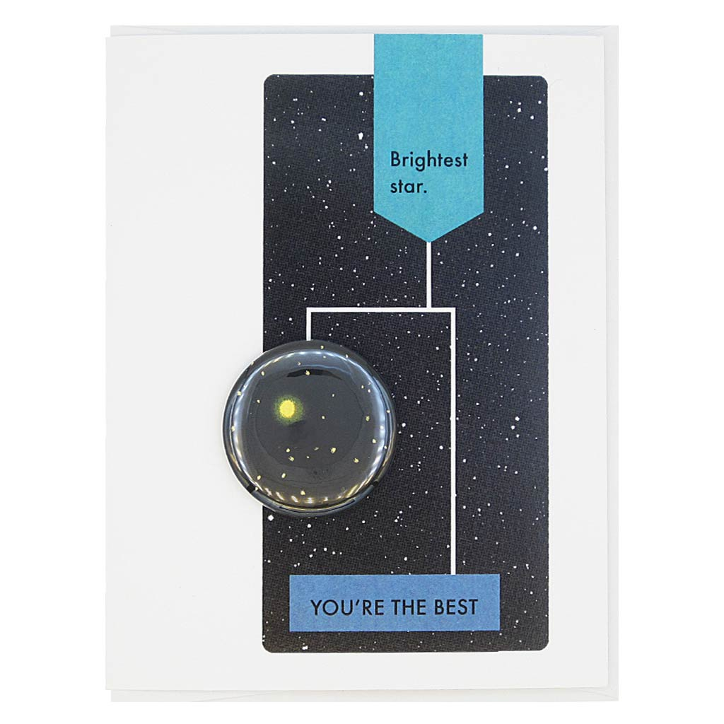 "This greeting card is designed to look like a page from a vintage science textbook with a black background of a starry sky. The text reads, 'Brightest Star' with an arrow to the text 'You're the Best' with an arrow to a 1½"" button Stars in the Night Sky that can be taken off and worn by the recipient. Card measures 4¼"" x 5½"", comes with a white envelope & is blank inside. Designed by The Regional Assembly of Text."