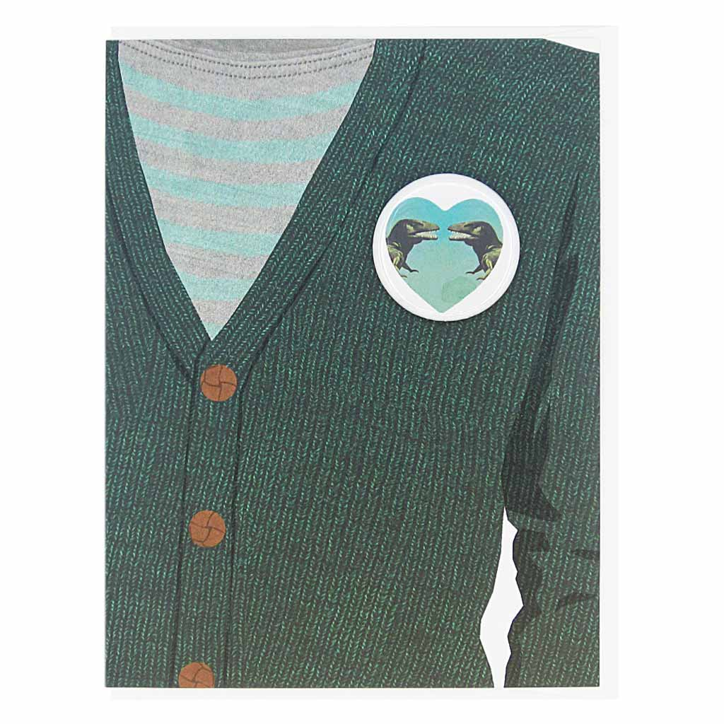 "This greeting card is a collage of a dark green cardigan with a button of a heart with two dinosaurs looking at eachother on the chest.  The button is 1¼"" and can be taken off and proudly worn by the recipient. Card measures 4¼"" x 5½"", comes with a white envelope & is blank inside. Designed by The Regional Assembly of Text."