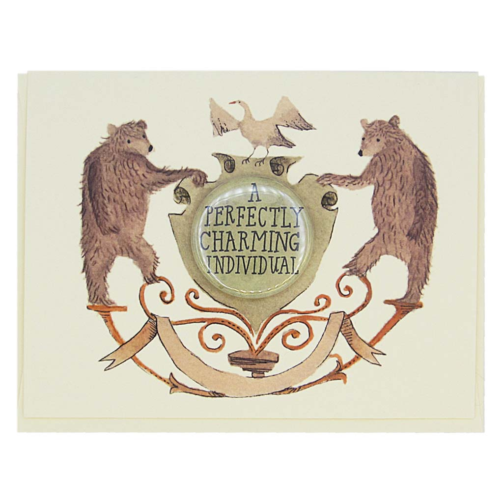 "This lovely card features a watercolour painting of two bears on either side of a crest. There is a 1½"" button in the middle of the crest that reads 'a perfectly charming individual'. The button can be taken off and worn by the recipient. Card measures 4¼"" x 5½"", comes with a cream envelope & is blank inside. Designed by The Regional Assembly of Text."
