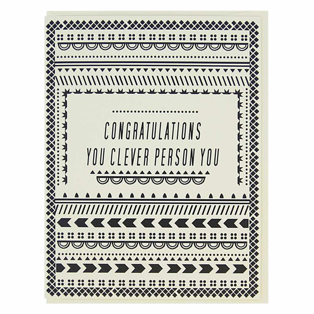 "This card has black geometric patterns on a cream coloured background with text in the middle that reads, 'Congratulations you clever person you'. Measures 4¼"" x 5½"", comes with a cream envelope & is blank inside. Designed by The Regional Assembly of Text."