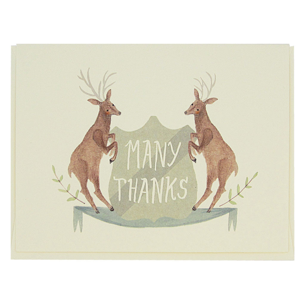 "This beautiful thank you card features a watercolour painting of two deer on either side of a crest that reads 'Many Thanks'. Card measures 4¼"" x 5½"", comes with a cream envelope & is blank inside. Designed by The Regional Assembly of Text."