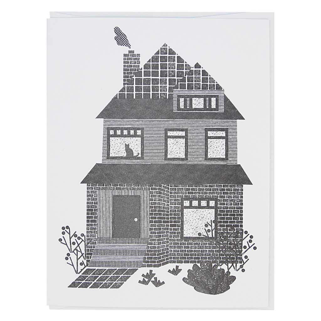 "This greeting card is a black and white image of two storey house with a cat in the top floor window. It has a lino cut feel. Card measures 4¼"" x 5½"", comes with a white envelope & is blank inside. Designed by The Regional Assembly of Text."