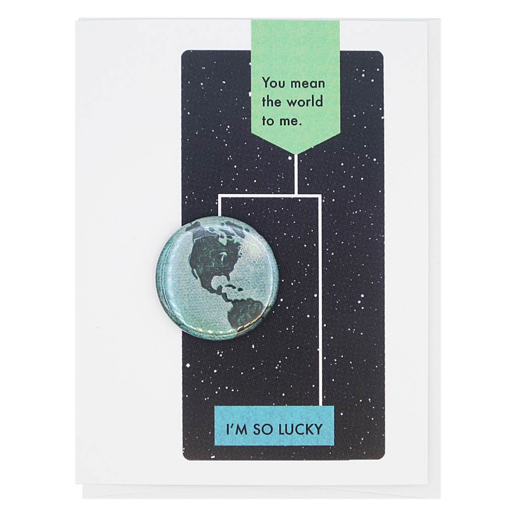 "This card is designed to look like a page from a vintage science textbook with a black background of a starry sky. The text reads, 'You Mean the World to Me' with an arrow to the text 'I'm so Lucky' with an arrow to a 1¼"" button of the earth that can be taken off and worn by the recipient. Card measures 4¼"" x 5½"", comes with a white envelope & is blank inside. Designed by The Regional Assembly of Text."