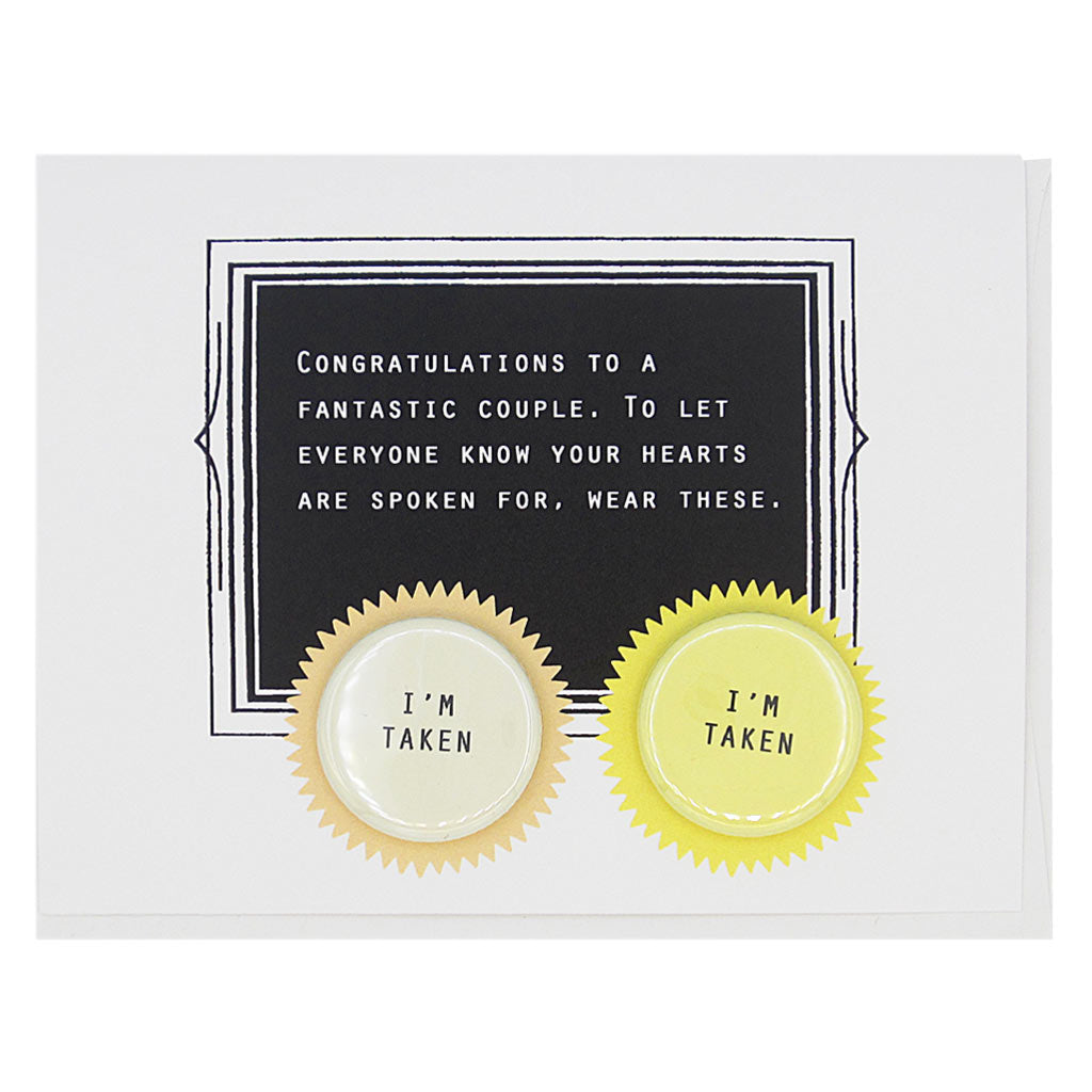 "This card celebrates finding love. The text reads,  'Congratulations to a fantastic couple. To let everyone know your hearts are spoken for, wear these'. And it features two 1¼"" buttons with the text 'I'm Taken' that can be taken off and proudly worn by the recipient. Card measures 4¼"" x 5½"", comes with a white envelope & is blank inside. Designed by The Regional Assembly of Text."