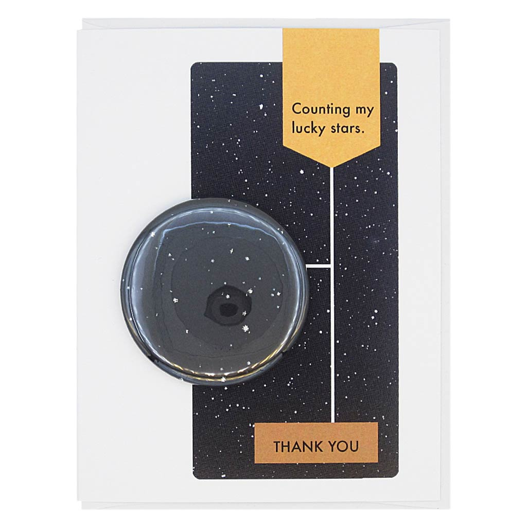 "This thank you card is designed to look like a page from a vintage science textbook with a black background of a starry sky. The text reads, 'Counting my Lucky Stars' with an arrow to the text 'Thank You' with an arrow to a 2¼"" button of a starry sky that can be taken off and worn by the recipient. Card measures 4¼"" x 5½"", comes with a white envelope & is blank inside. Designed by The Regional Assembly of Text."