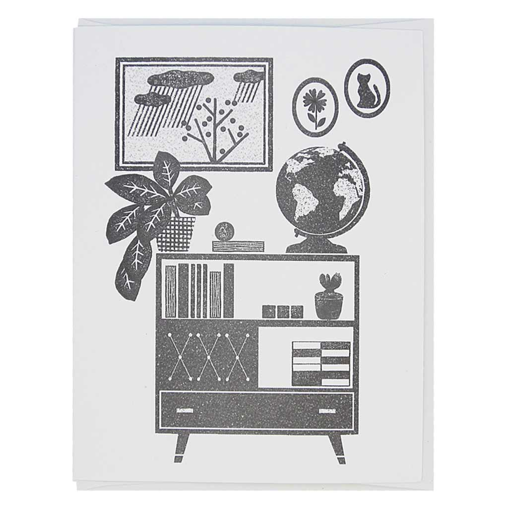 "This greeting card is a black and white image of a mid century modern bookshelf with a globe, plants, books with some paintings on the wall behind it. It has a lino cut feel. Card measures 4¼"" x 5½"", comes with a white envelope & is blank inside. Designed by The Regional Assembly of Text."