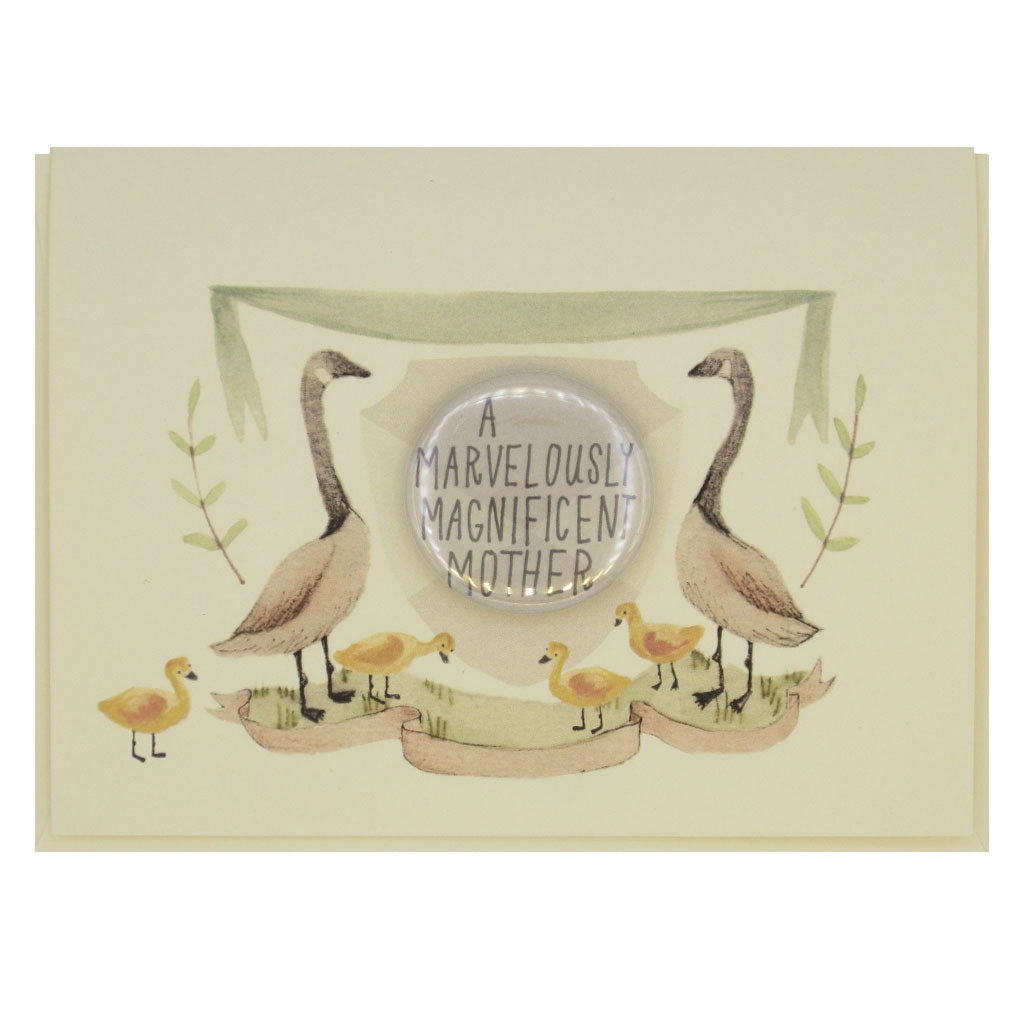 "This lovely card features a watercolour painting of two geese and some goslings on either side of a crest. There is a 1½"" button in the middle of the crest that reads 'a marvelously magnificent mother'. The button can be taken off and worn by the recipient. Card measures 4¼"" x 5½"", comes with a cream envelope & is blank inside. Designed by The Regional Assembly of Text."