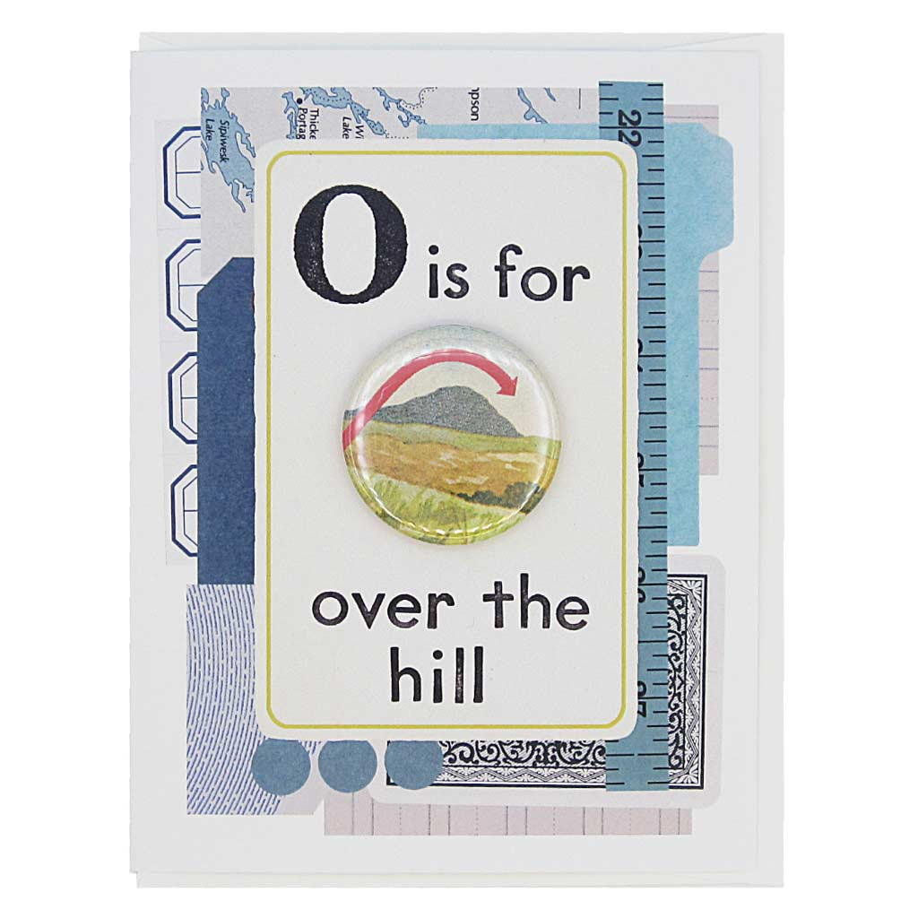 "This birthday card looks like a vintage flashcard and says O is for Over the Hill. It features a 1½"" button of a hill with an arrow going over it that can be taken off and worn by the recipient. Card measures 4¼"" x 5½"", comes with a white envelope & is blank inside. Designed by The Regional Assembly of Text."