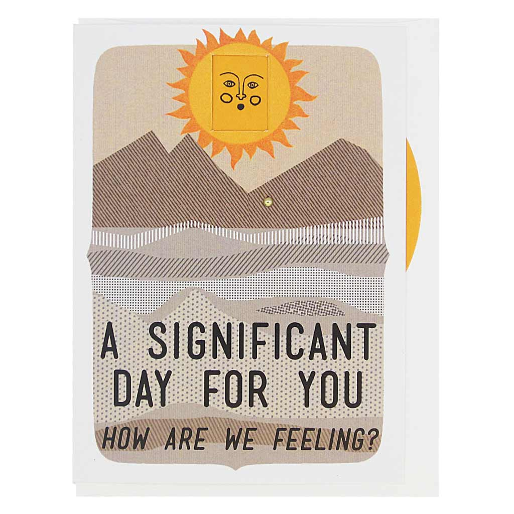 "This greeting card features a landscape with a sun on the horizon. The sun has a face and you can turn a wheel to find an appropriate facial expression for this occasion. The card reads, 'A Significant Day for You… how are we feeling?' There are 8 faces to choose from: sad, mad, worried, smiling, winking, frowning etc. Card measures 4¼"" x 5½"", comes with a white envelope & is blank inside. Designed by The Regional Assembly of Text."