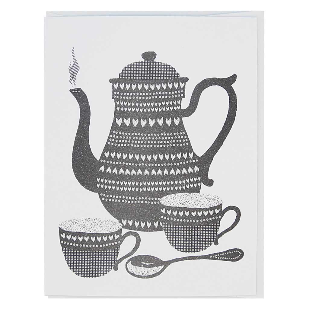 "This greeting card is a black and white image of two cups of tea and a teapot. It has a lino cut feel. Card measures 4¼"" x 5½"", comes with a white envelope & is blank inside. Designed by The Regional Assembly of Text."