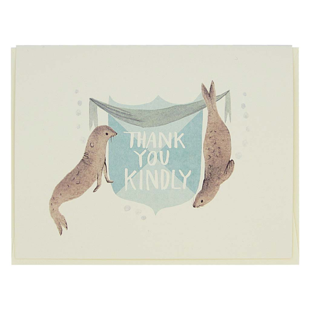 "This beautiful thank you card features a watercolour painting of two seals on either side of a crest that reads 'Thank You Kindly'. Card measures 4¼"" x 5½"", comes with a cream envelope & is blank inside. Designed by The Regional Assembly of Text."