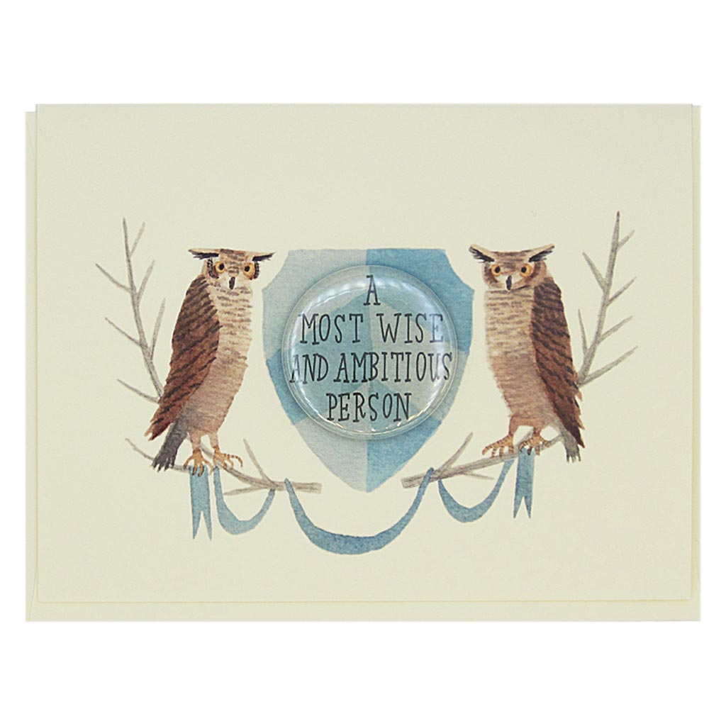 "This lovely card features a watercolour painting of two owls on either side of a crest. There is a 1½"" button in the middle of the crest which reads 'a most wise and ambitious person'. The button can be taken off and worn by the recipient. Card measures 4¼"" x 5½"", comes with a cream envelope & is blank inside. Designed by The Regional Assembly of Text."