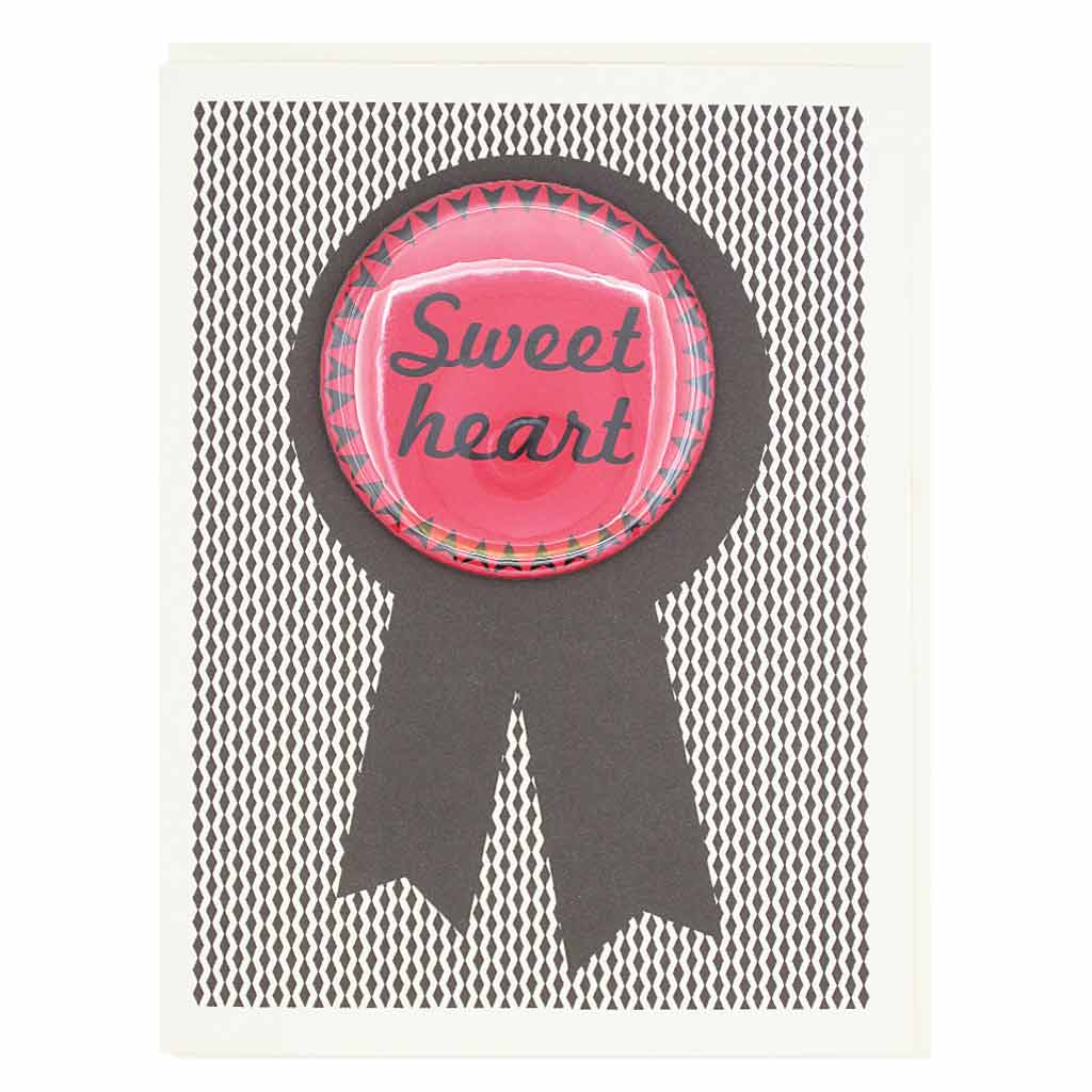 "This card is sure to please your sweetheart. Features a 2¼"" button that says ""Sweet Heart"" that can be taken off and proudly worn by the recipient. Card measures 4¼"" x 5½"", comes with a cream envelope & is blank inside."