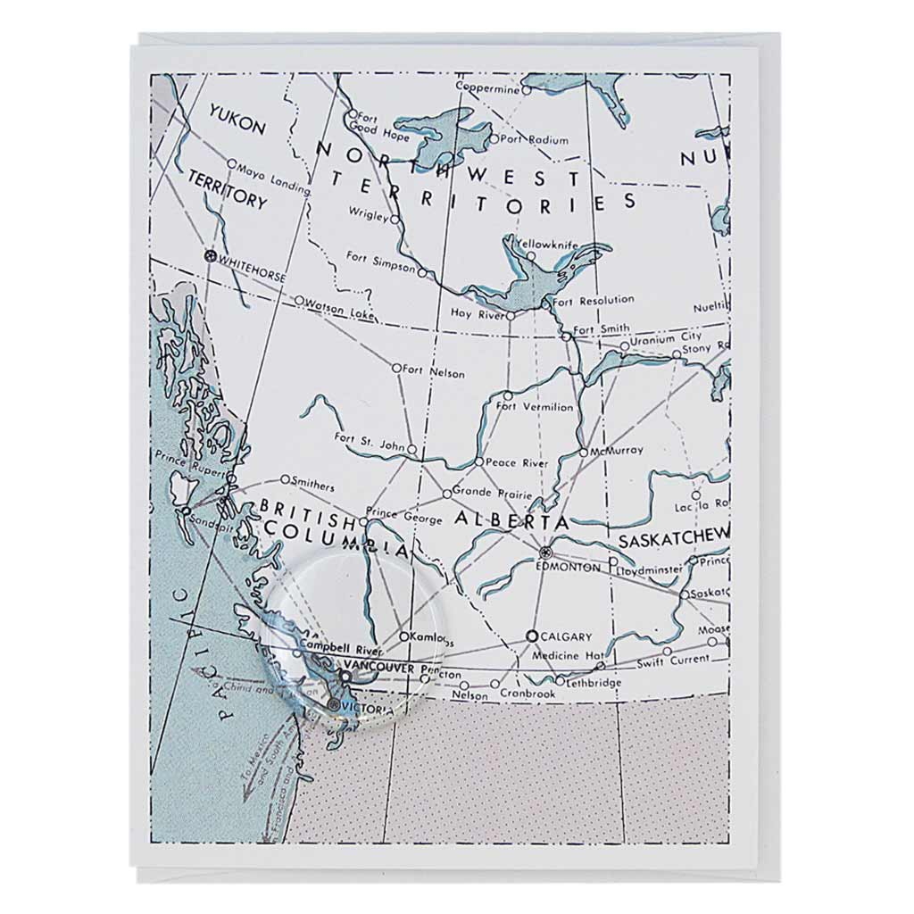 "This greeting card is a blue, black and white map of British Columbia with a 1½"" button of Victoria and Vancouve B.C. Card measures 4¼"" x 5½"", comes with a white envelope & is blank inside. Designed by The Regional Assembly of Text."