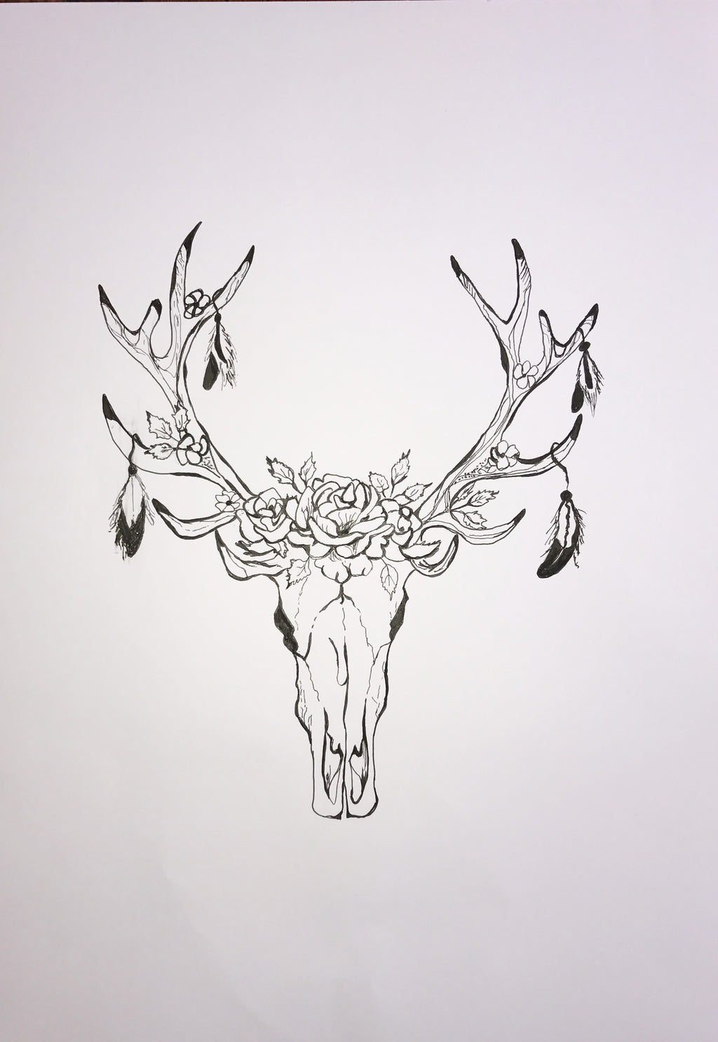 Hand drawn black and white deer skull adorned with feathers and roses.