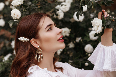 woman with ornate hair clip looking at flowers