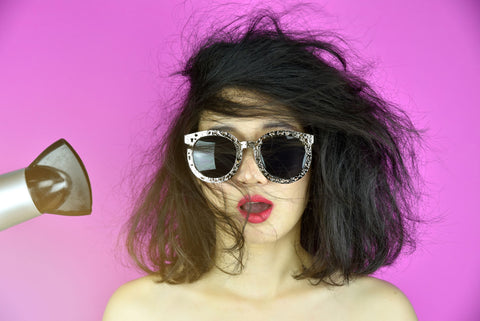 woman wearing sunglasses on purple background blow-drying her hair