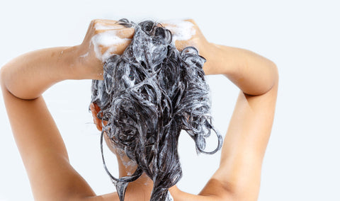 a woman shampooing her hair in the shower