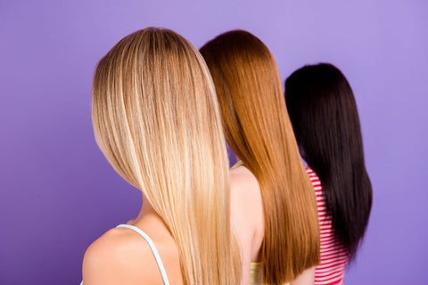 The back of women's heads. One blonde, one redhead and one brunette