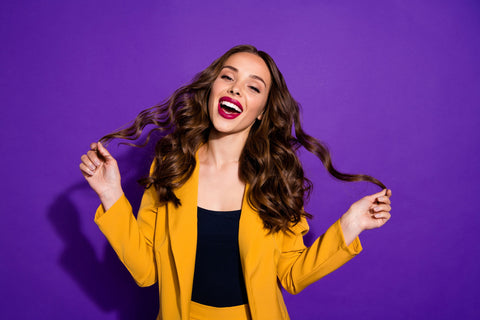 brunette woman smiling and holding curly hair on purple background