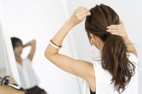 woman with dark hair fixing her ponytail in the mirror