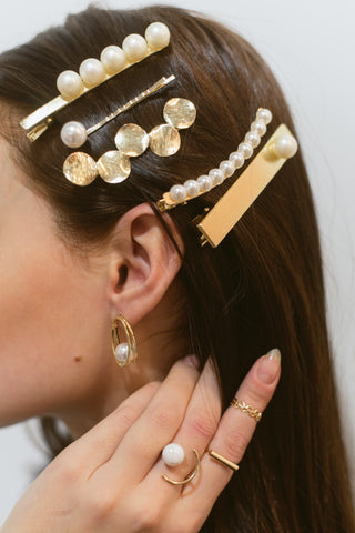 a woman modeling many gold and pearl clips in her hair