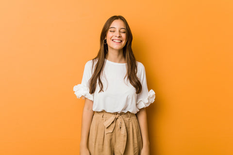 woman smiling on an orange background