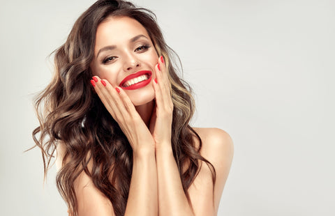 woman with red nails and lips smiling with hands on her face