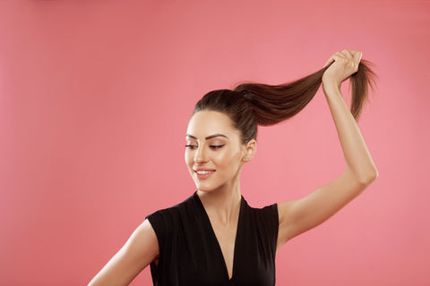 woman holding up hair by her ponytail