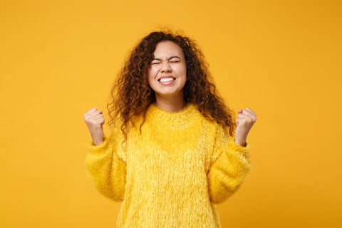 "happy woman making a ""yes"" gesture on orange background"