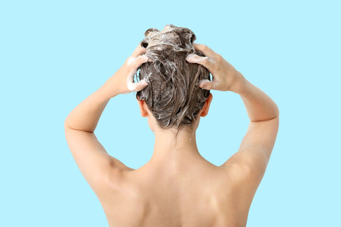 woman shampooing hair on light turquoise background