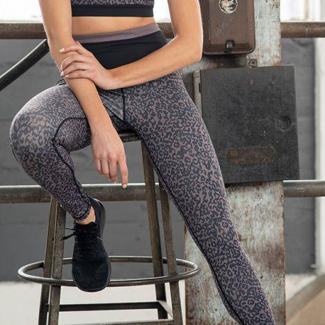 Model sitting on a stool wearing leopard-print Warpony leggings.