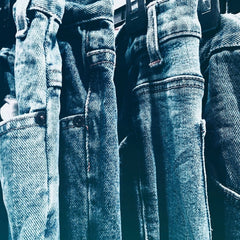 This is an image of many jeans hanging back to back.