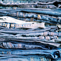 A closeup image of jeans folded and stacked on top of themselves. This image is used in the J.Forks Designs Blog about denim.