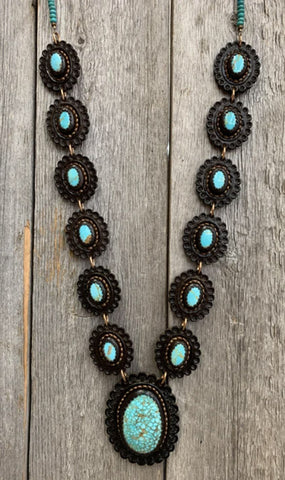 J.Forks Designs Necklace with turquoise hand set into leather. This necklace was hanging on a wooden backdrop in the j.forks designs' boutique located on main street in Boerne Texas.
