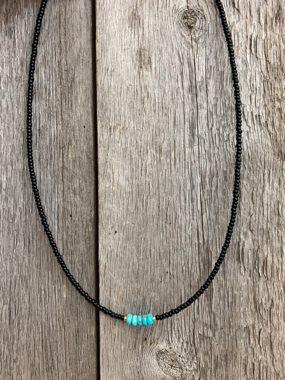 "J.Forks Designs necklace hanging on a wooden backdrop. This 16"" necklace has black seed beads with a Kingman Turquoise center."