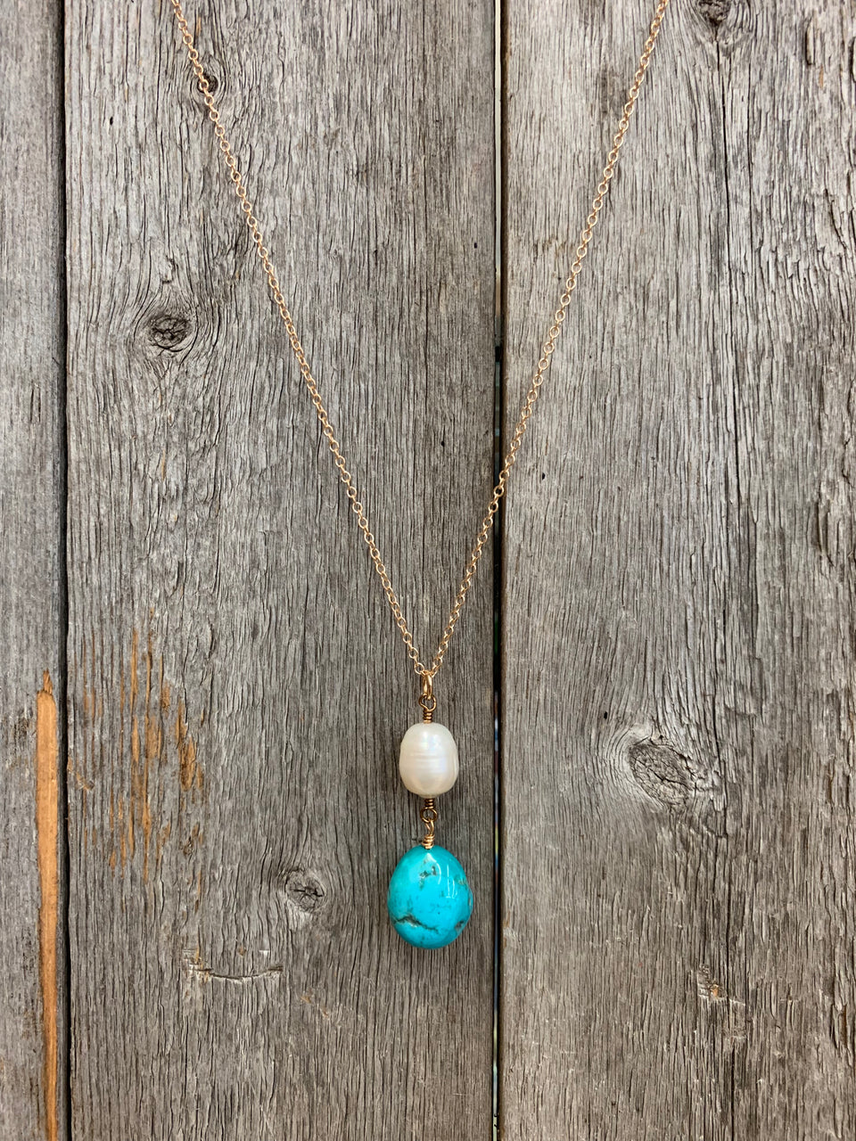 "J.Forks Designs necklace hanging on a wooden backdrop. This necklace is an 18"" bronze chain with freshwater pearl and Bisbee Turquoise Nugget drop and bronze lobster claw clasp."