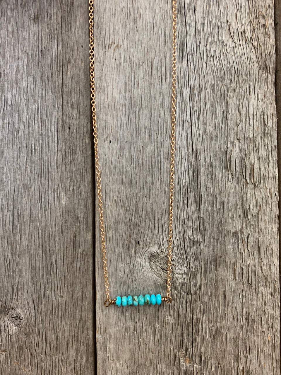 "J.Forks Designs necklace hanging on a wooden backdrop. The necklace is 16"" bronze chain with Kingman Turquoise center and bronze lobster claw clasp."