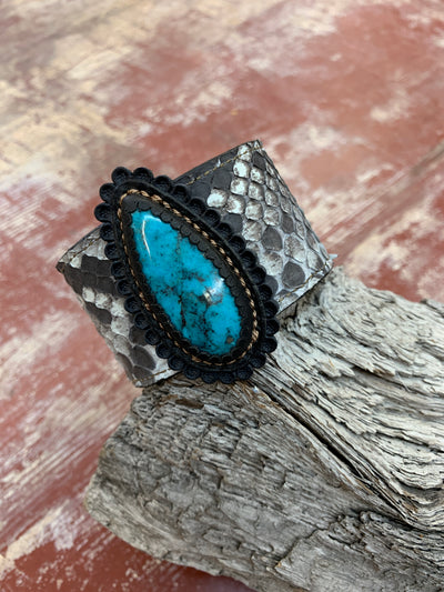"J.Forks Designs 1 1/2"" wide Natural Python Cuff with a 45-carat Bisbee Turquoise stone that is hand set in black leather. The bracelet is placed on a wooden stump and showcases the turquoise stone."
