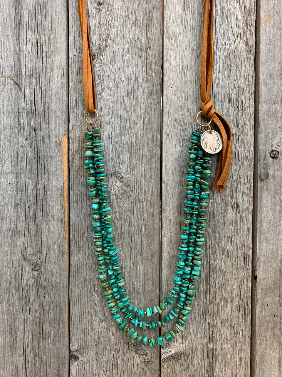 "J.Forks Designs necklace hanging on wooden backdrop. This necklace is 32"" Kingman Chip Turquoise with Buffalo Nickel Side Drop and Cognac Leather Back"