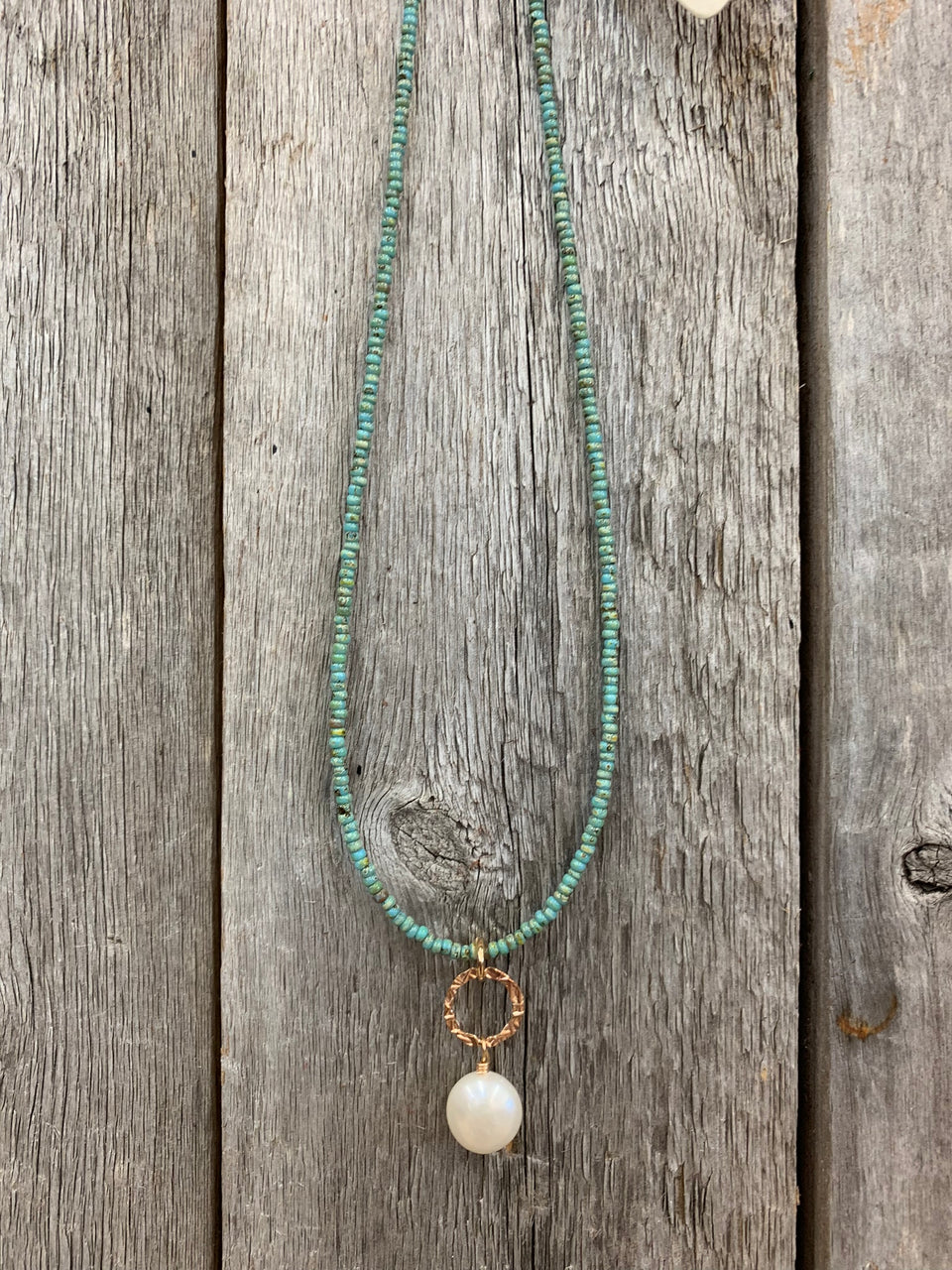 "J.Forks Designs necklace hanging on a wooden backdrop. This is a 16"" turquoise seed beads necklace with a hammered bronze ring and freshwater pearl drop."