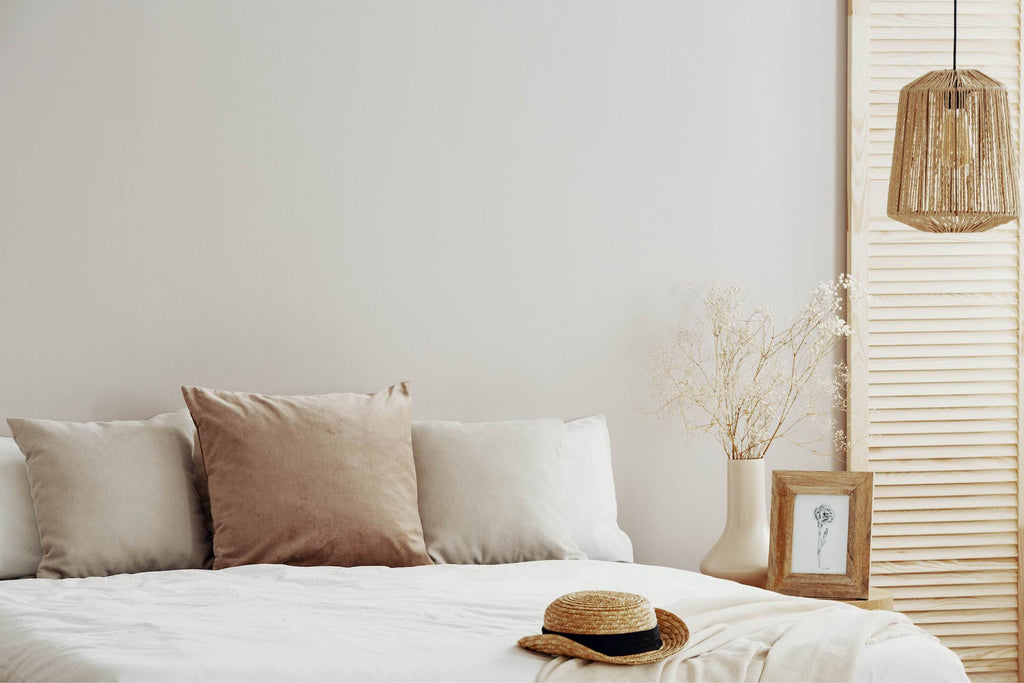 Beautiful guest room with premium quality bedding and a straw hat on the bed