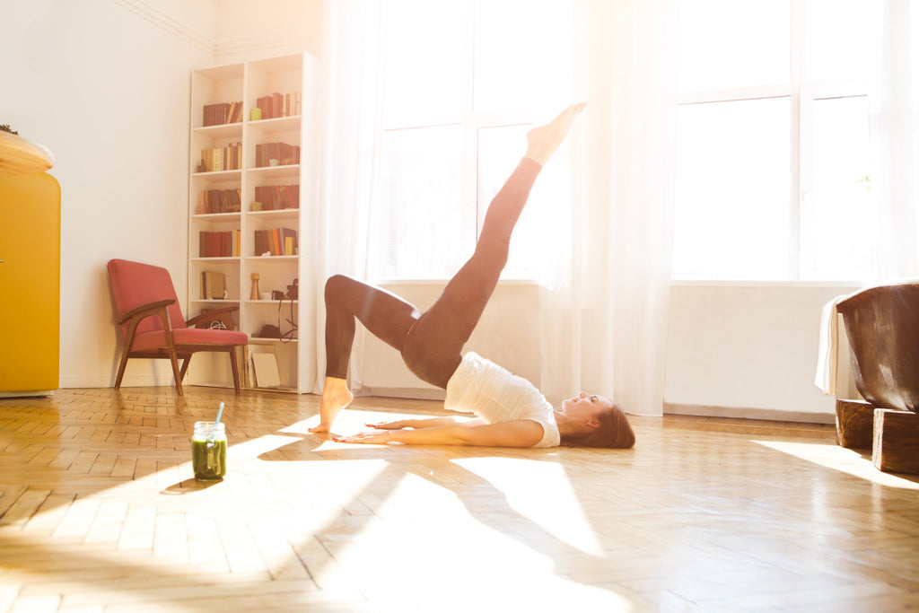 Woman doing yoga on her wooden floor in the morning sun