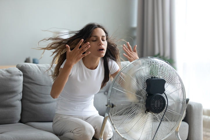 Woman with fan on her face