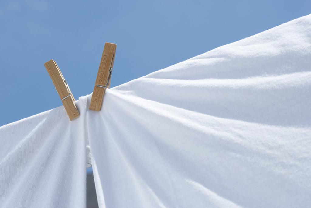White sheets pegged on a clothesline against a blue sky.